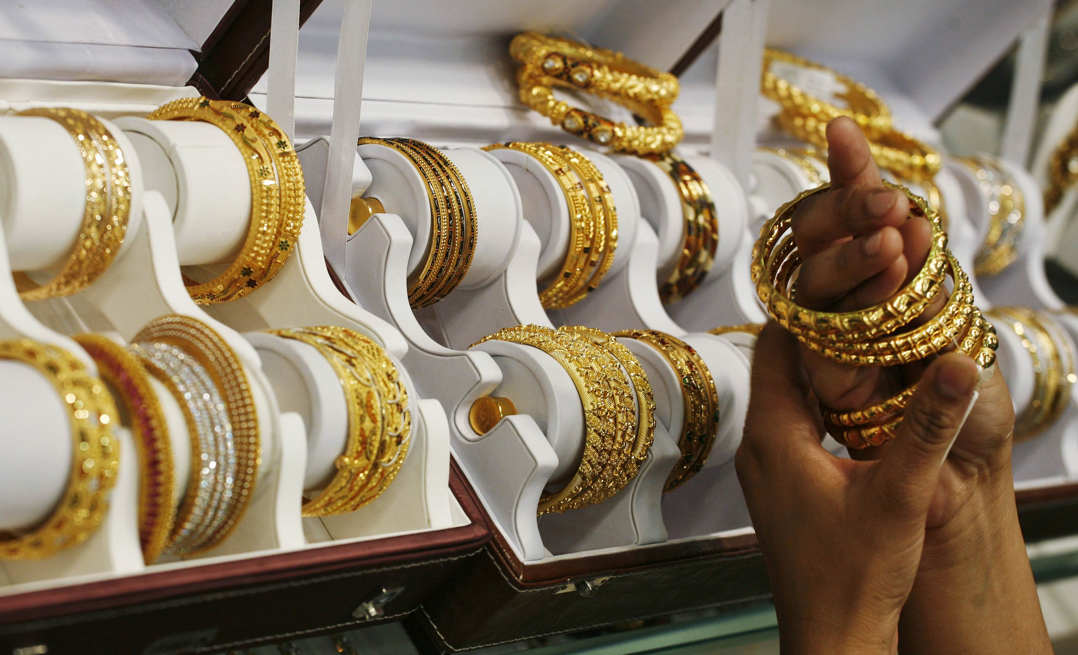 A customer tries gold bangles inside a jewellery showroom at Noida in the northern Indian state of Uttar Pradesh in this April 21, 2011 file photo. India's passion for gold is putting such a strain on state finances that the government may slap higher import taxes on the precious metal, but demand buoyed by heady inflation and meagre savings will blunt the impact of any rise in duties as reported January 16, 2013.  REUTERS/Parivartan Sharma/Files (INDIA - Tags: BUSINESS COMMODITIES)